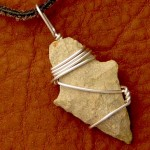 Arrowhead pendant photographed on a leather purse background (wirewrapped by Rena Klingenberg).