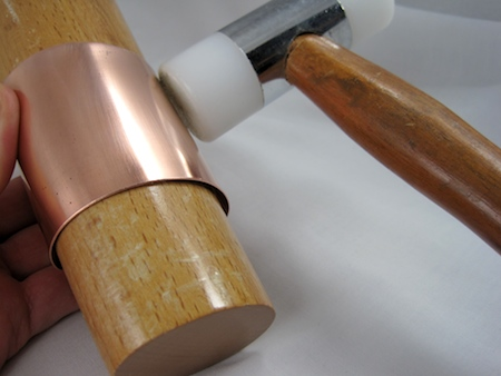 Hammering the copper bracelet on the mandrel