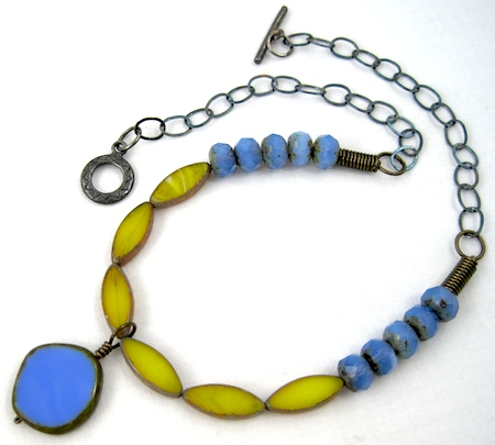 Coiled crimp bead covers in action - between the last blue bead and the beginning of the chain, on each side of this necklace. (Necklace by Rena Klingenberg.)