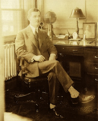 Inventor of the expansion bracelet, Art Hadley, seated at his desk. He's 28 years old. Year 1913.