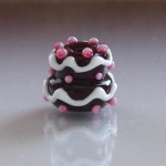 Chocolate Cake Bead with White Frosting and Raspberry Dots