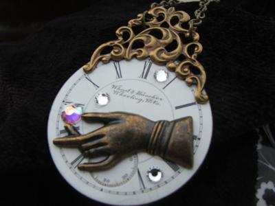 Joan Williams' Hand of Time Pendant suggests the time-travel theme in steampunk jewelry.