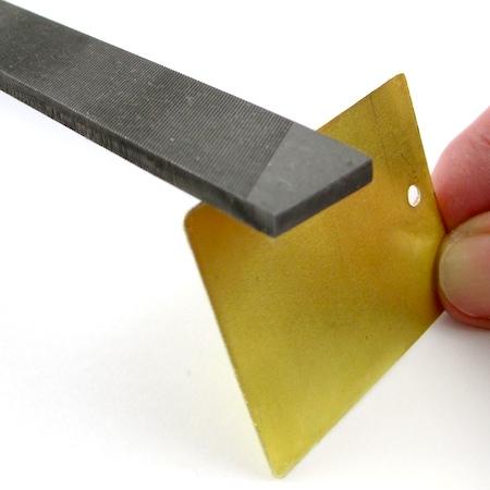 Filing edges of pendant blanks for Easy Riveted Pendant - tutorial by Rena Klingenberg