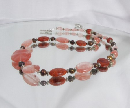 A unique handmade necklace crafted by hand from a collection of Strawberry Quartz and semi-precious Coral