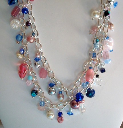 I just grabbed handfulls of my leftover pinks, blues, whites, some pearls, used headpins and put them on this heavy silver chain. Its 40 inches long, can be doubled