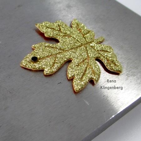 Colocando ilhó de metal na folha de tecido para brincos de folha de outono coloridos - tutorial por Rena Klingenberg