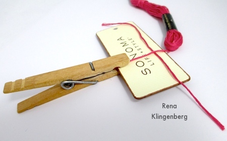 Clipping the cord end to the winding board - Colorful Tassel Jewelry - tutorial by Rena Klingenberg