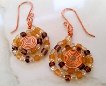 Dollar store e-beads (glass, but all wonky shaped) and scrap wire. My hands were rusty with the spirals but I like them anyway.
