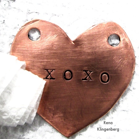 Wiping excess paste off of stamped metal heart - How to Give Metals an Oxidized Look - Tutorial by Rena Klingenberg