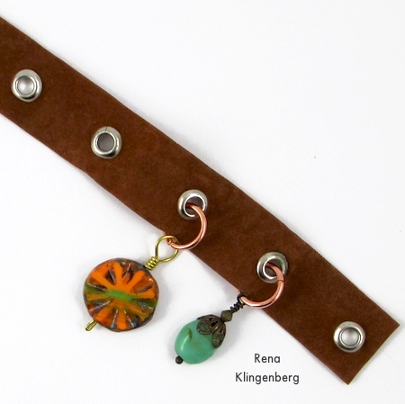 Attaching charms to the grommet tape - Grommet Wrap Charm Bracelet - Tutorial by Rena Klingenberg