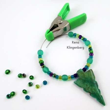 Use a clip to prevent beads from sliding off the wire - Memory Wire Pendant and Earrings - Tutorial by Rena Klingenberg